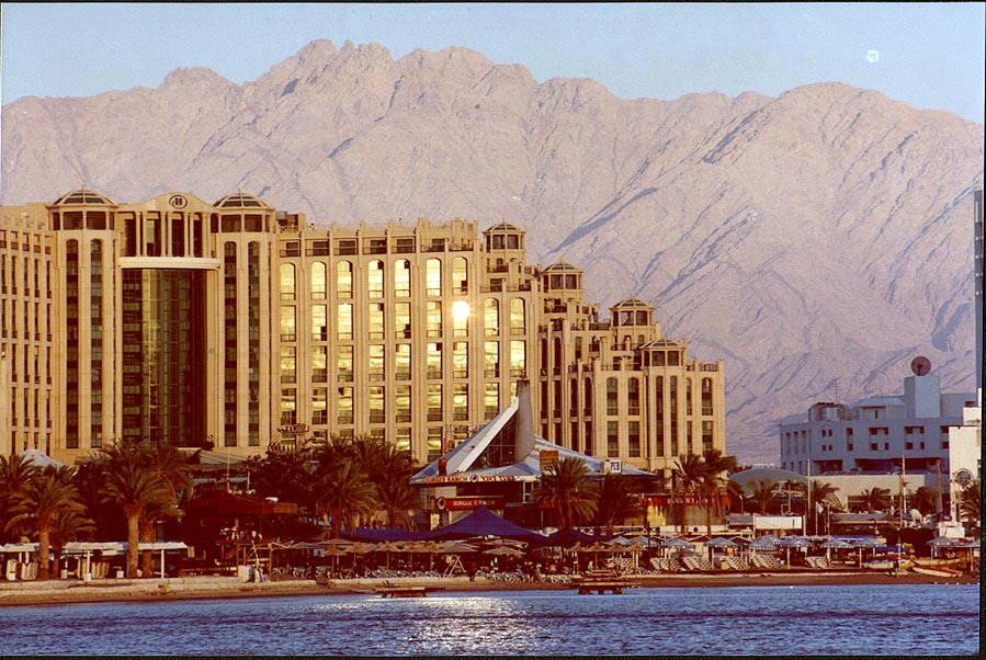 A hotel and a city beach during sunset, with Edom...behind them. Eilat, the Middle East