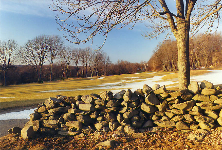 Abandoned stone wall and a golf course in northern Fall River at evening. Massachusetts