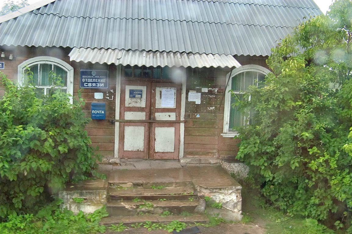 A post office in Izborsk, view from a tourist bus at rain. Russia