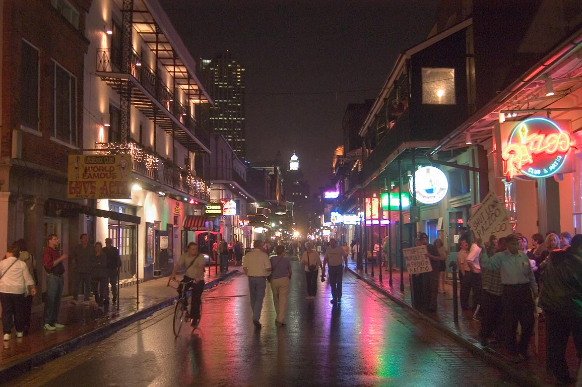 Bourbon Street near Conti St. at evening, with a...bar at right. New Orleans, Louisiana