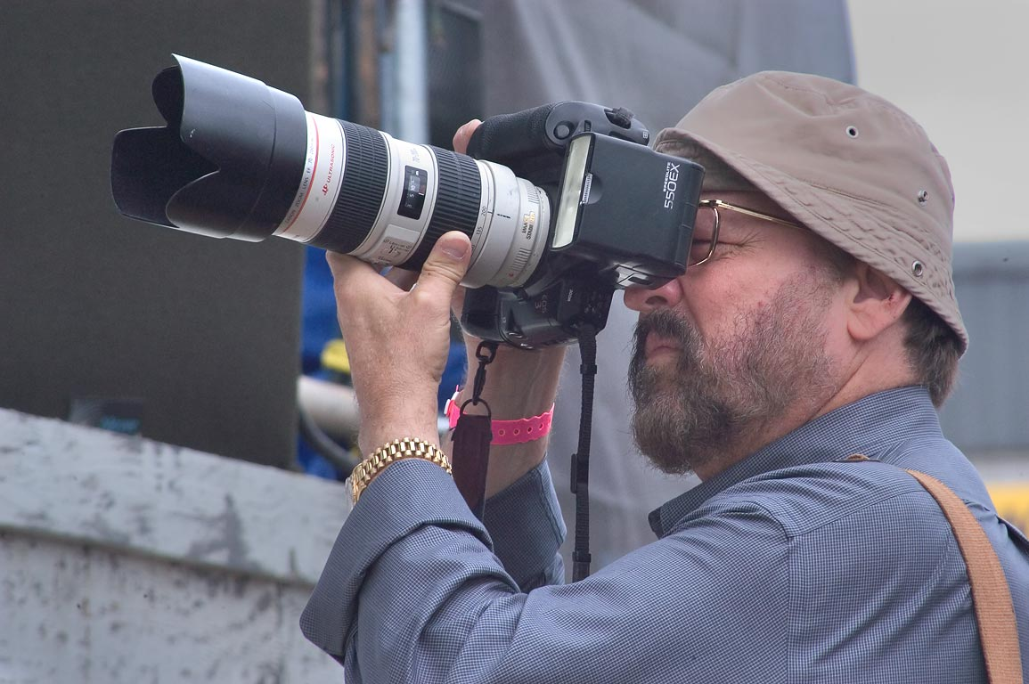 A spectator with a photo-camera near a stage during Jazzfest. New Orleans, Louisiana