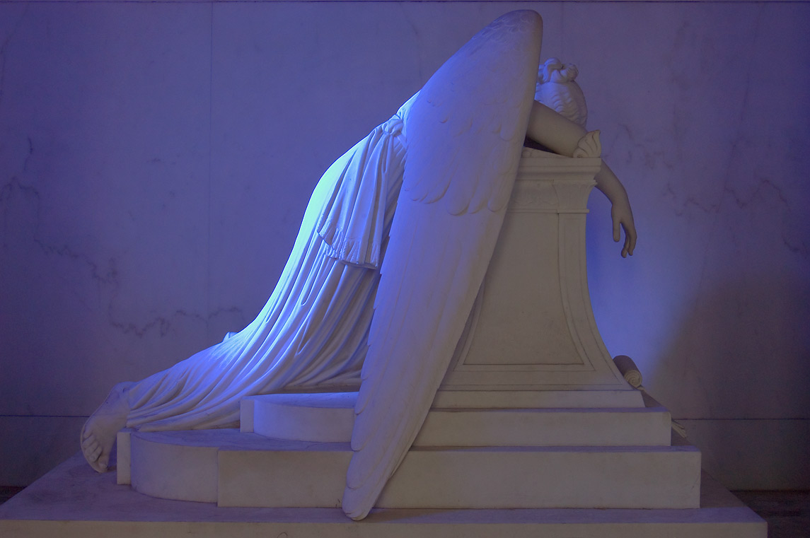 Weeping angel illuminated through blue tinted...Cemetery. New Orleans, Louisiana