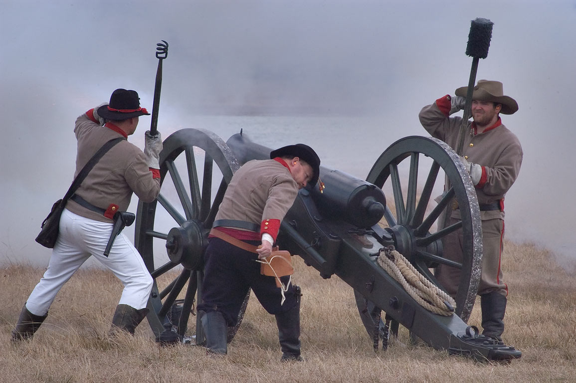 Firing from a cannon of Confederate artillery at...in background. Madisonville, Texas