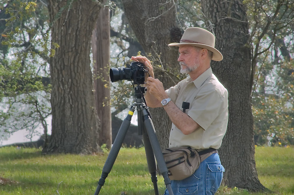 Photographer with a camera on a tripod in Old Bailor park. Independence, Texas