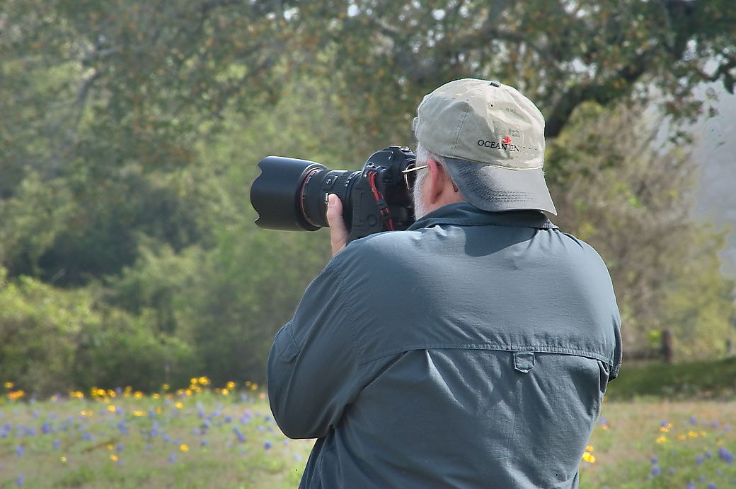 Photographer with a camera with a big lens taking...Old Bailor park. Independence, Texas