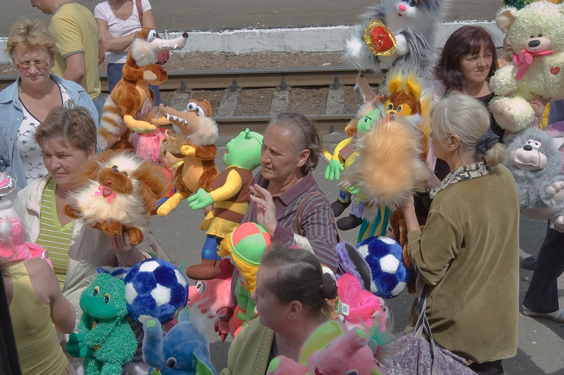 Merchants selling colorful soft toys an a...from a window of a train. Belorussia