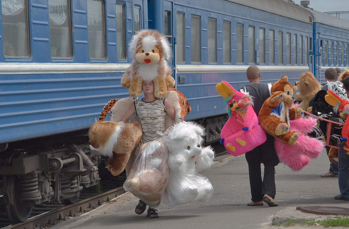 Man loaded with artificial fur soft toy animals on a train platform in Zhlobin. Belorussia