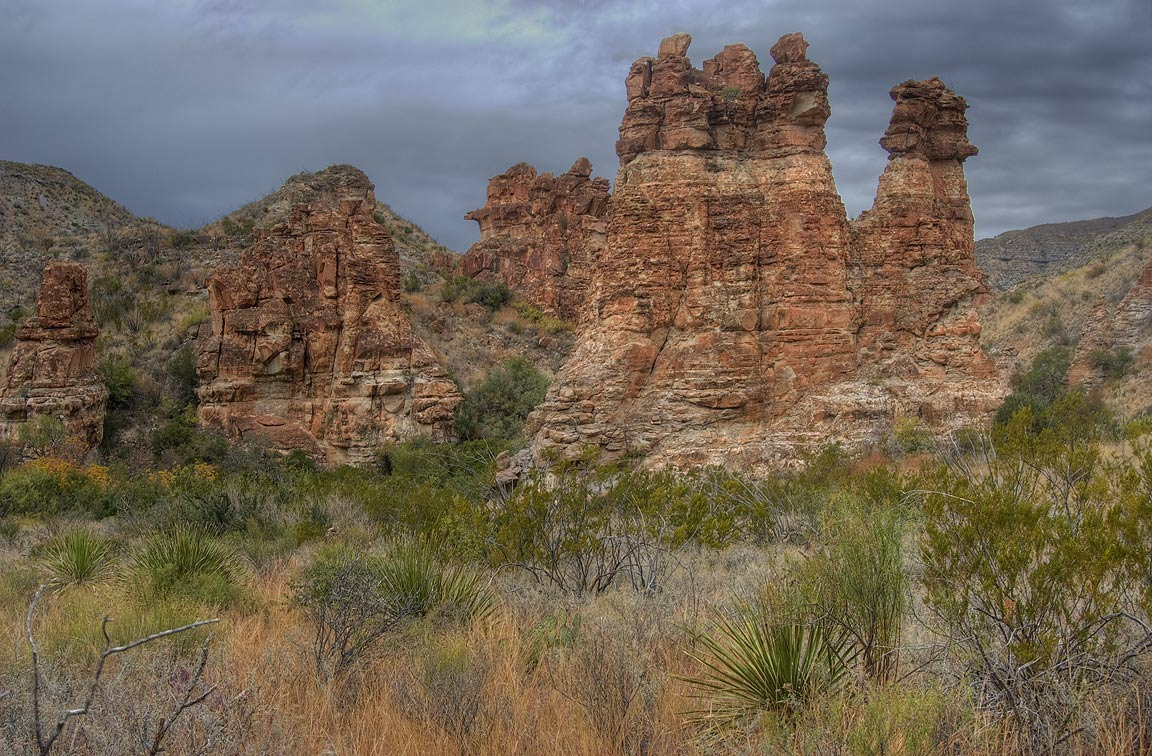 Eroded pinnacles of pink volcanic tuff looking...Creek Trail. Big Bend National Park