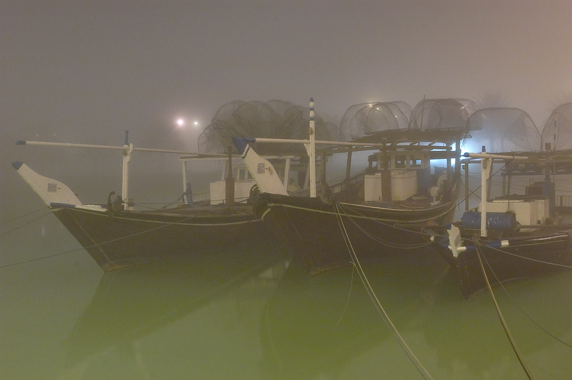 Dhow boats in port in fog at morning. Doha, Qatar
