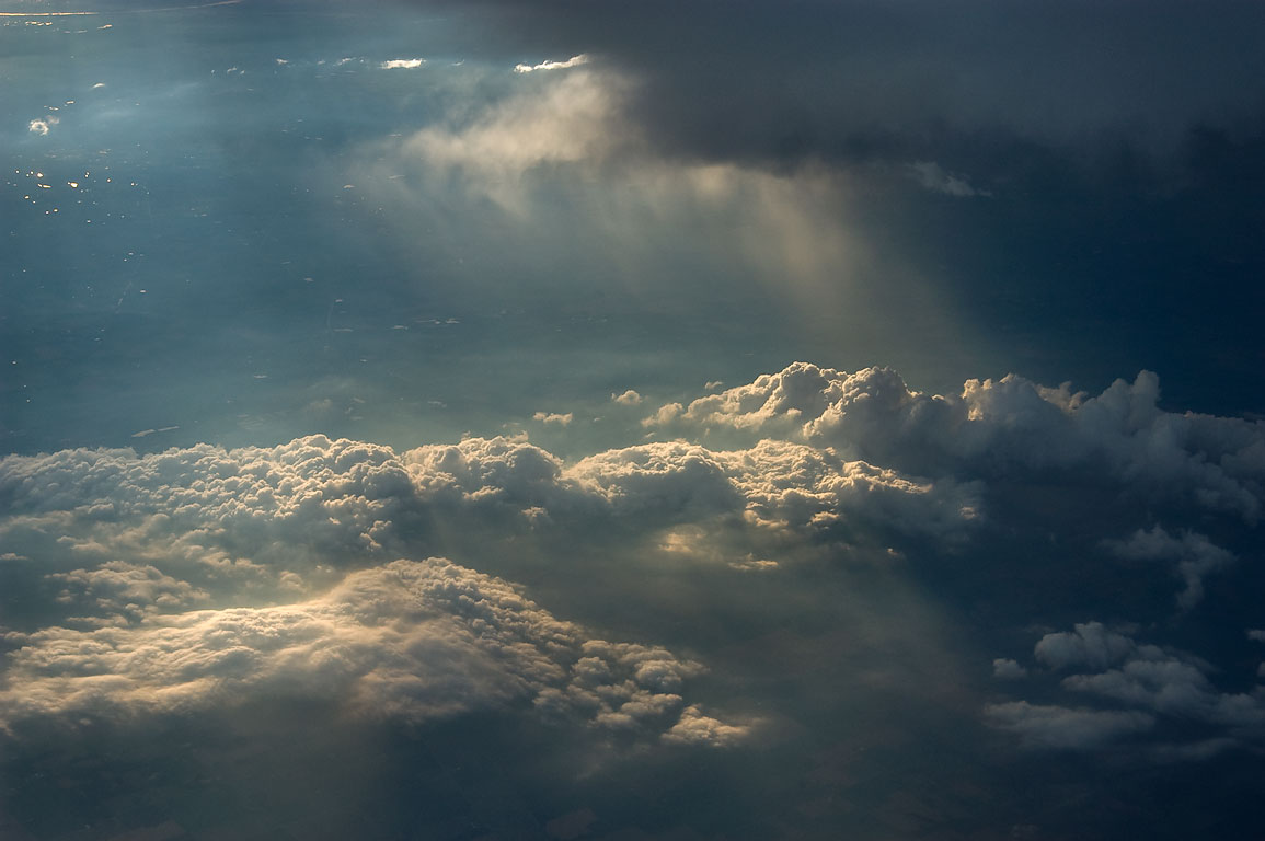 Sun behind clouds from a window of a plane from Houston to Moscow, Russia