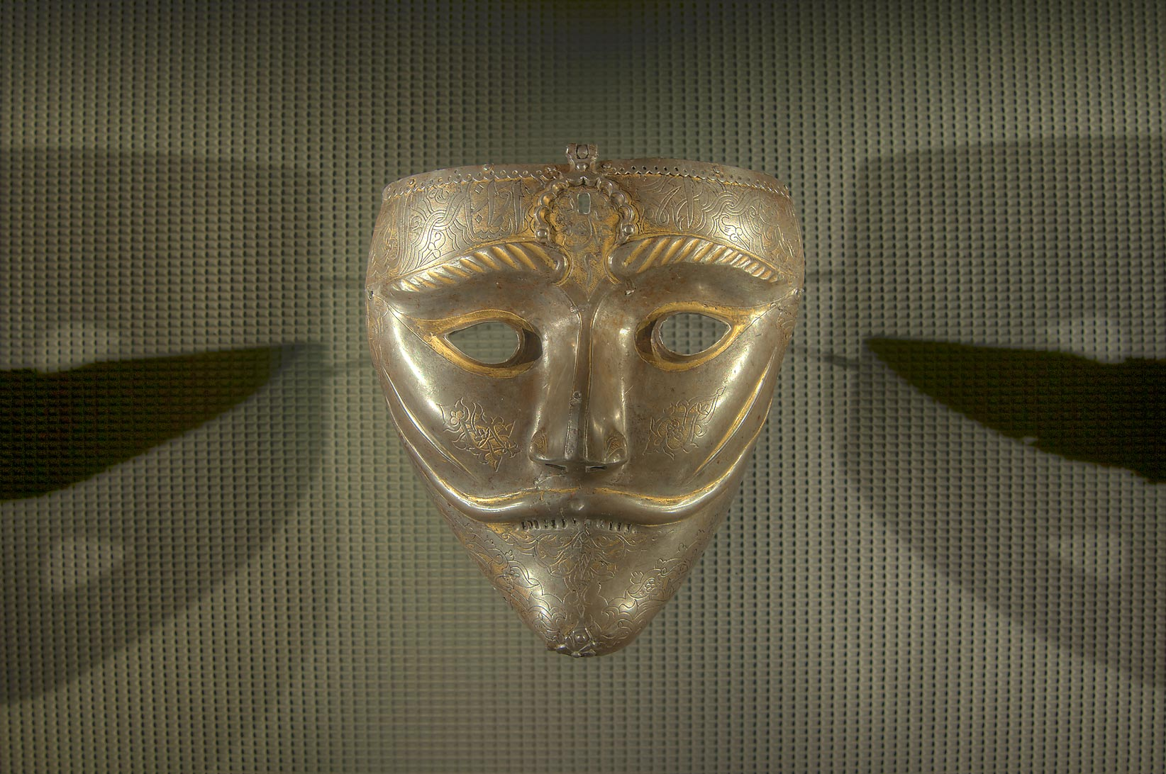 War mask (15th century, steel with gold inlay) on...in Museum of Islamic Art. Doha, Qatar