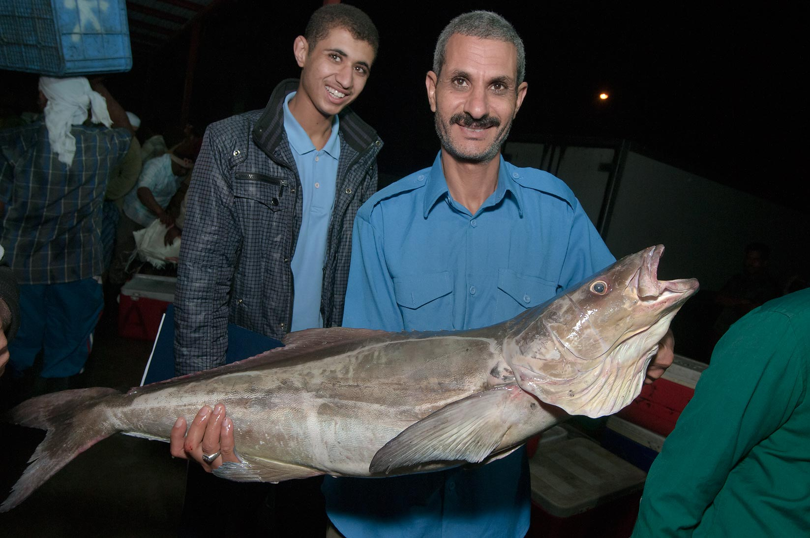 Fisherman with a large fish posing in wholesale Central Fish Market. Doha, Qatar