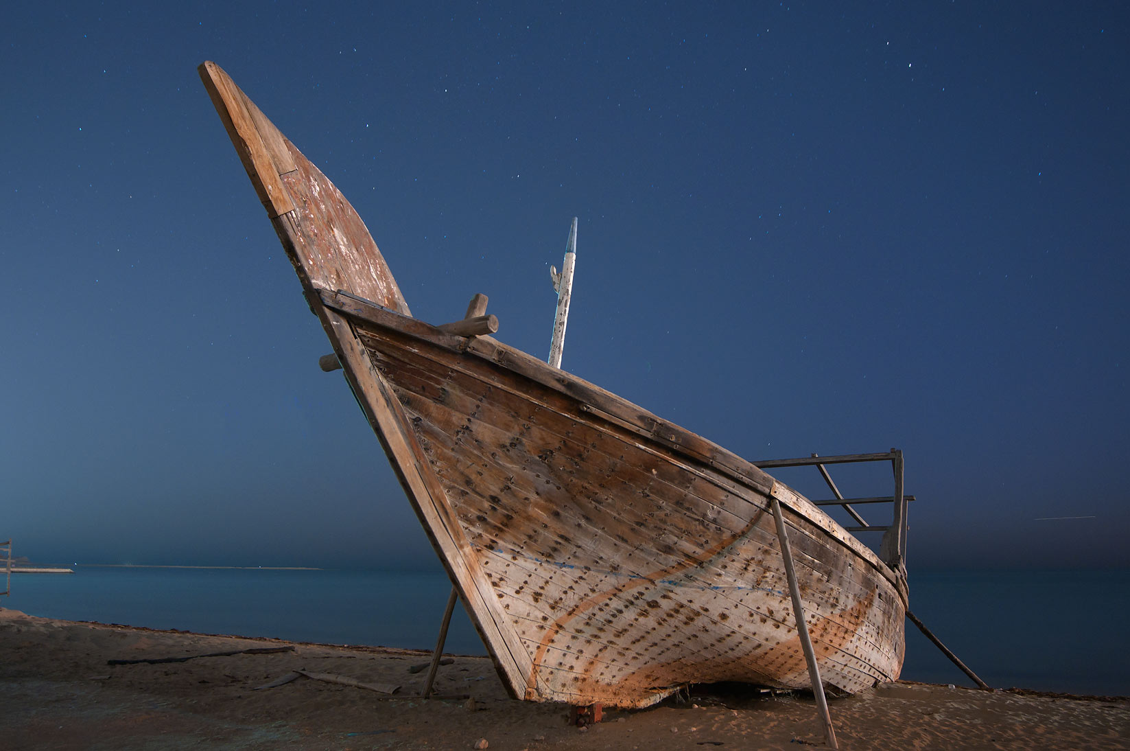 Dhow fishing boat on a beach in heritage village. Al Wakrah, Qatar