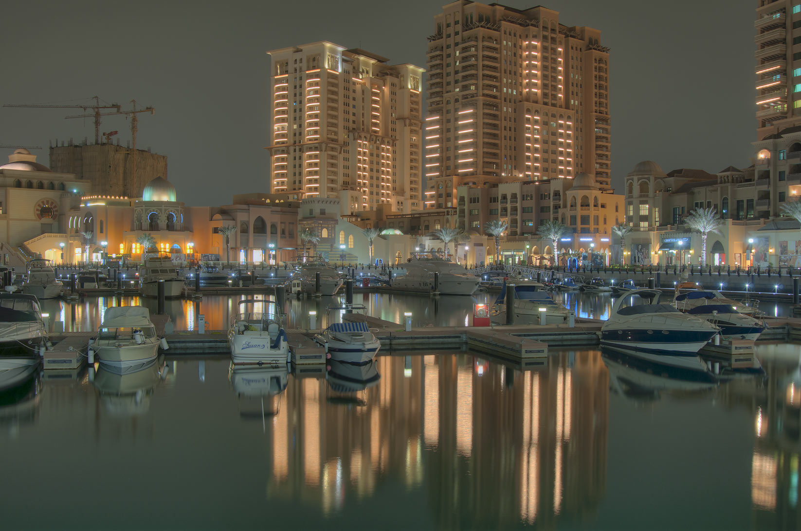Reflections of evening lights in a harbor of...Pearl Qatar development. Doha, Qatar