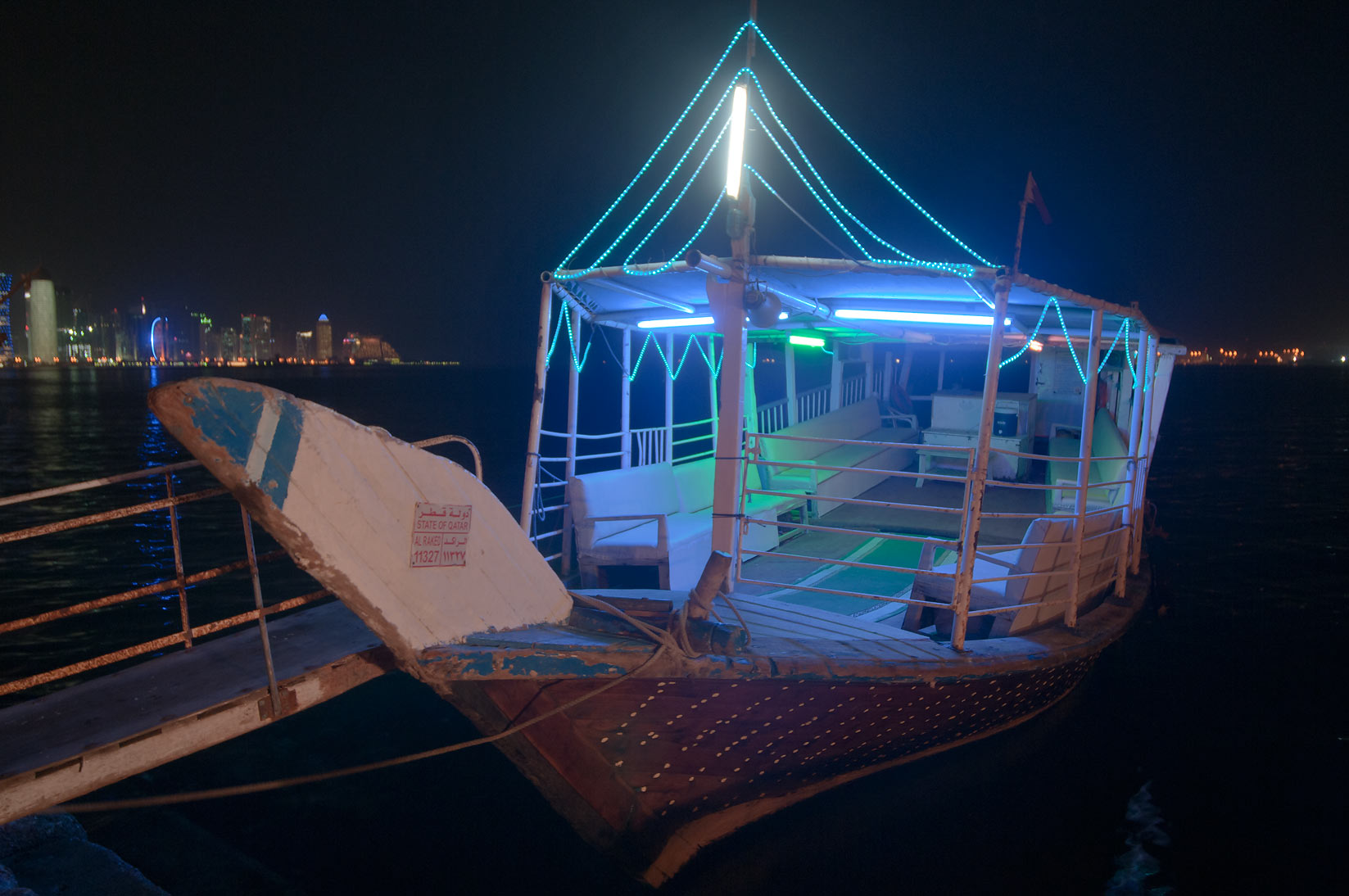 Illuminated dhow boat docked at Corniche. Doha, Qatar
