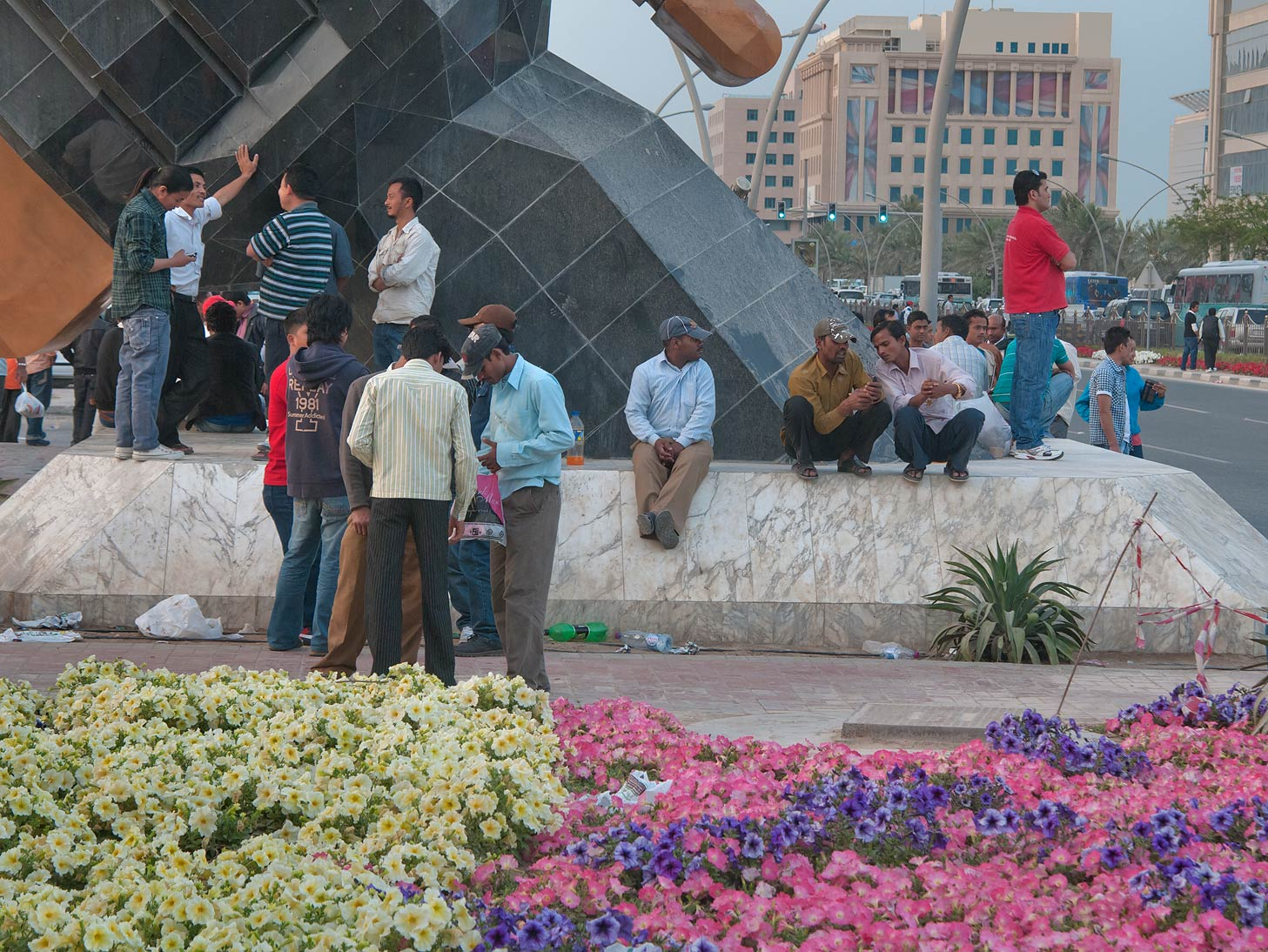 Migrant workers at a base of Sword Arch at Grand...Station on Friday evening. Doha, Qatar