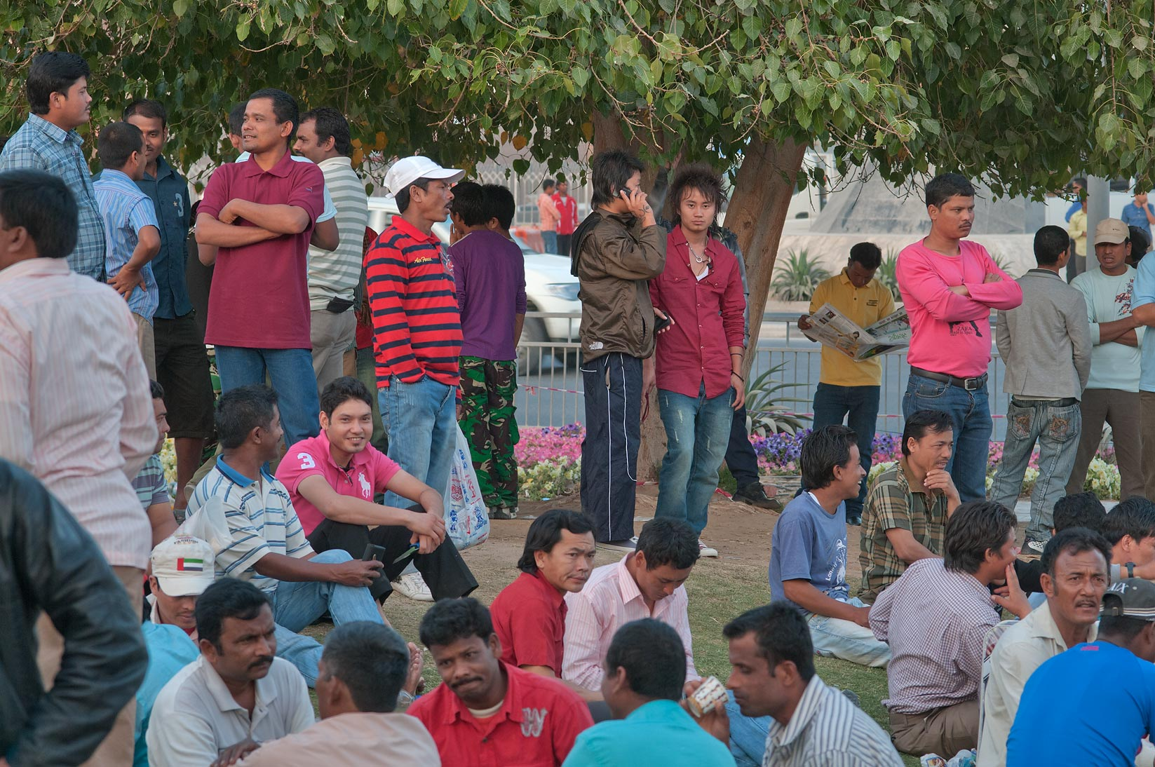 Migrant workers standing and sitting at Grand...Al Ghanim on Friday. Doha, Qatar