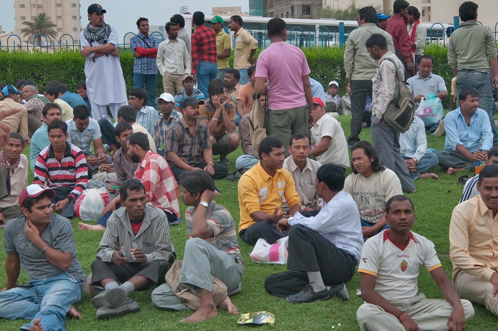 Workers resting on a lawn on Friday evening at Central Bus Station Al Ghanim. Doha, Qatar