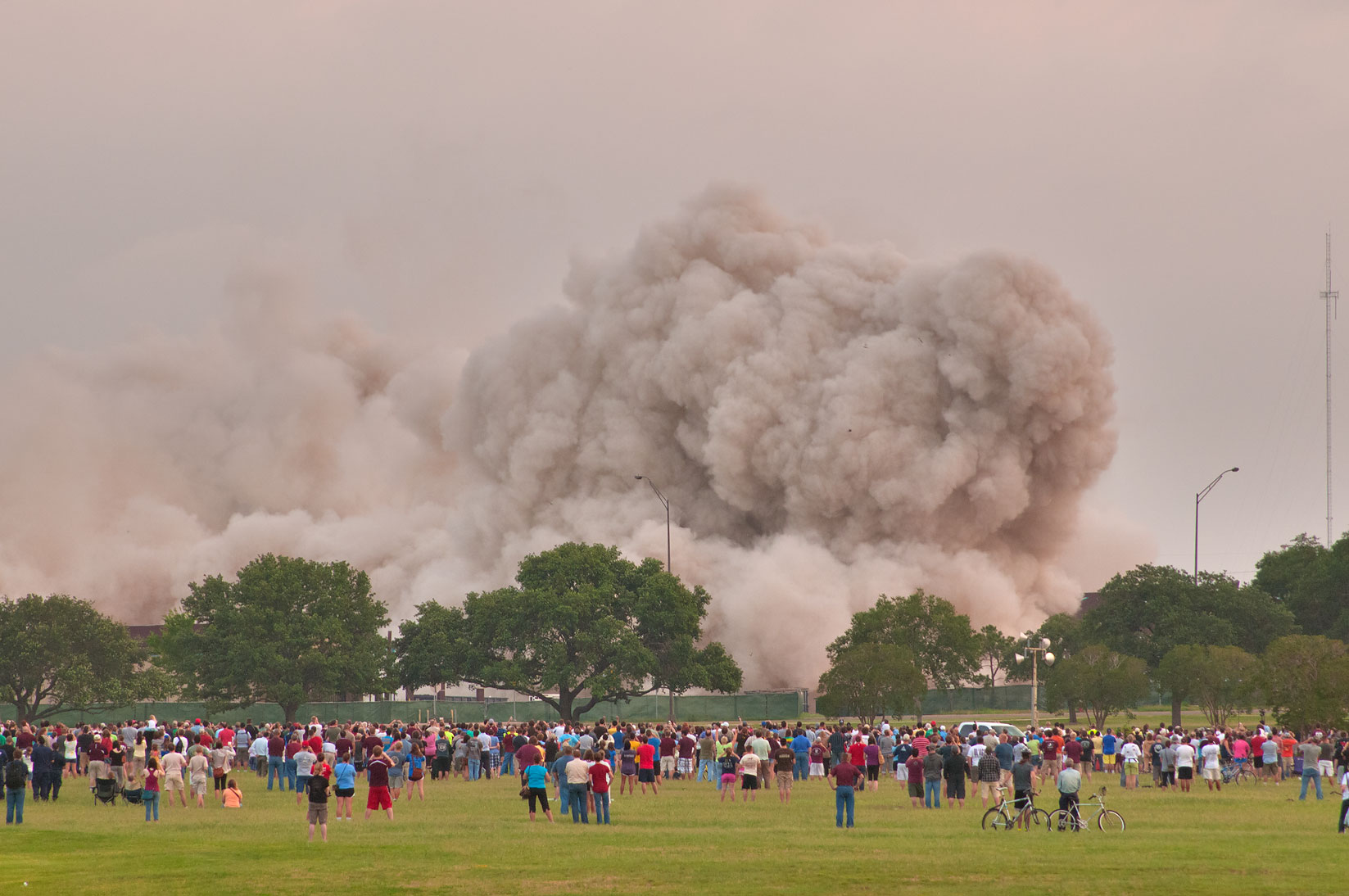 Gawkers looking on dust from implosion of Plaza Hotel (Ramada Inn). College Station, Texas