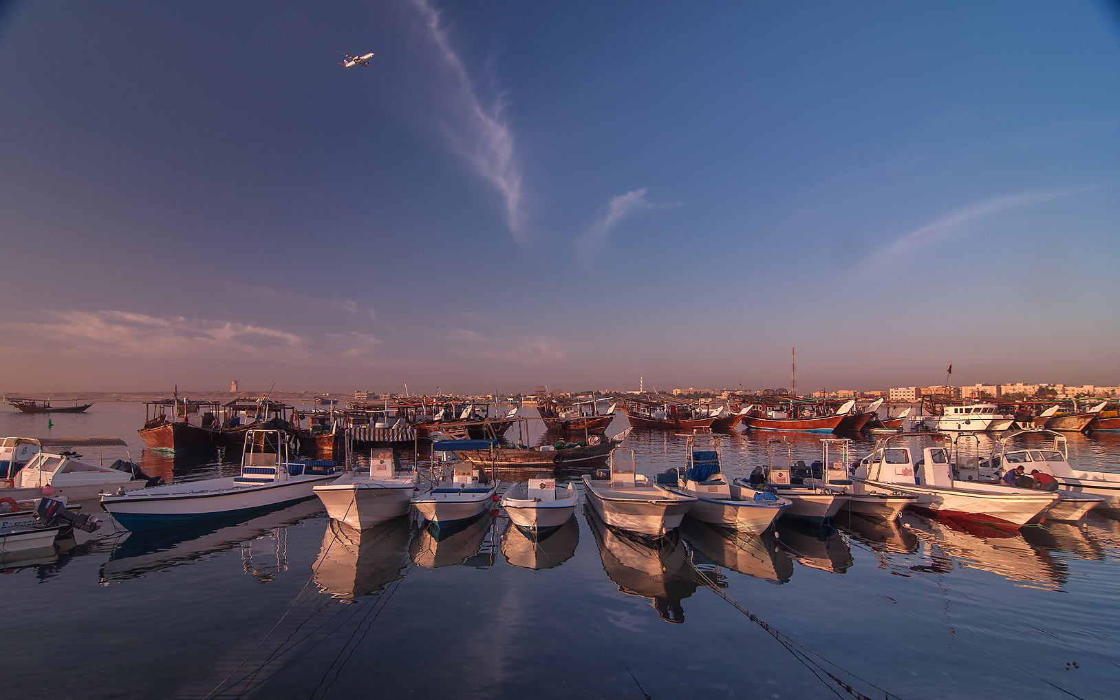 Rows of fishing boats in harbor in Al Wakra at sunrise, with airplane in background. Qatar