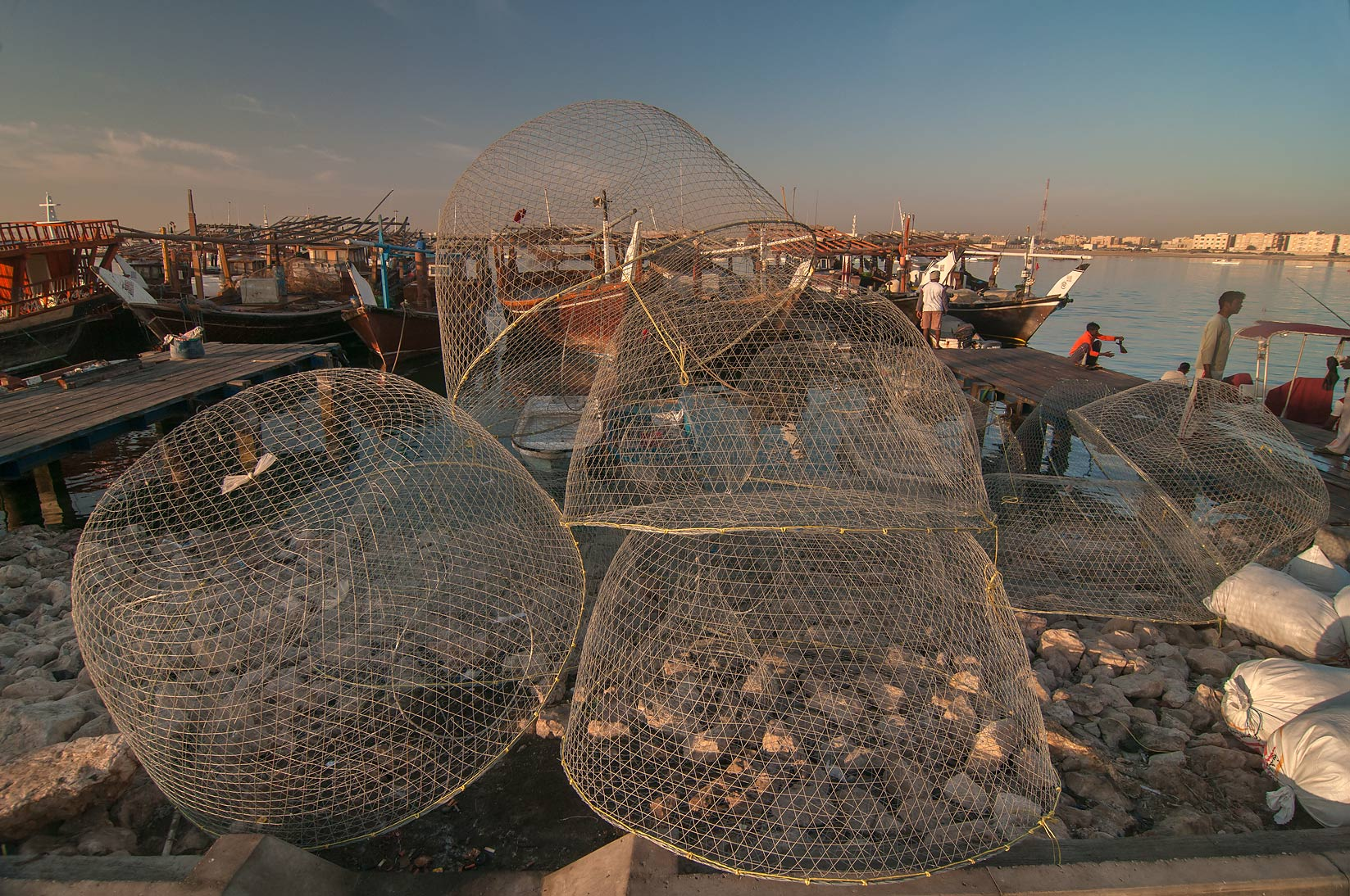 Domed wire fish traps (gargoor) and fishing boats in Al Wakra. Qatar