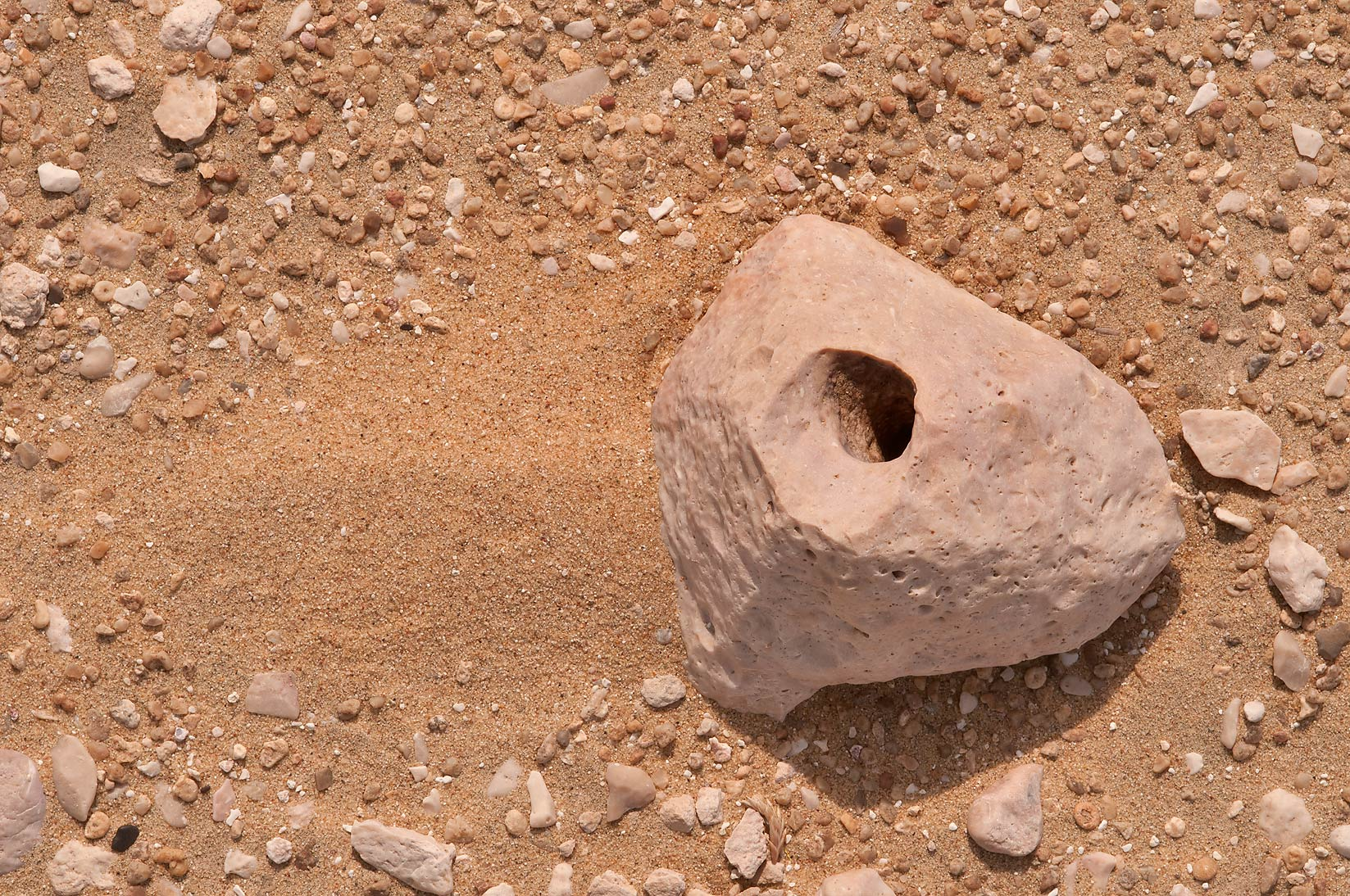 Flint stone with a wind carved hole on desert...Mesayeed, south-west from Doha. Qatar