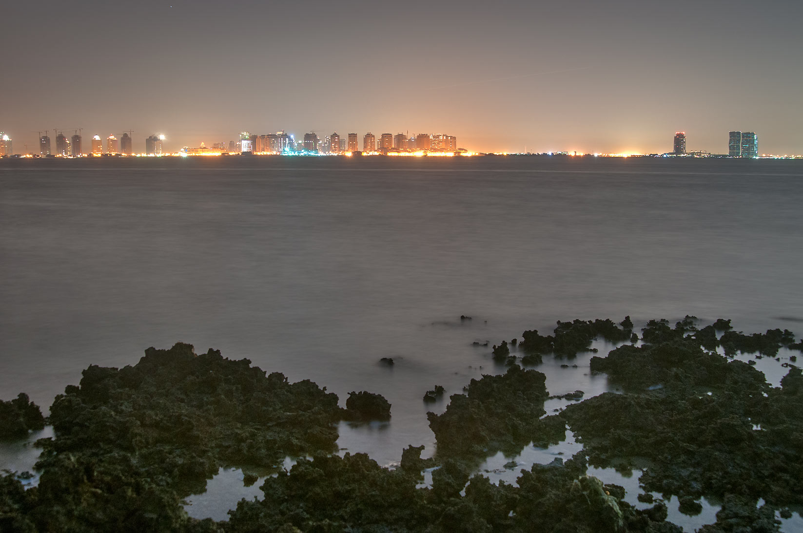 Lights of Pearl Qatar Development from Al Aaliya Island near Doha after sunset. Qatar