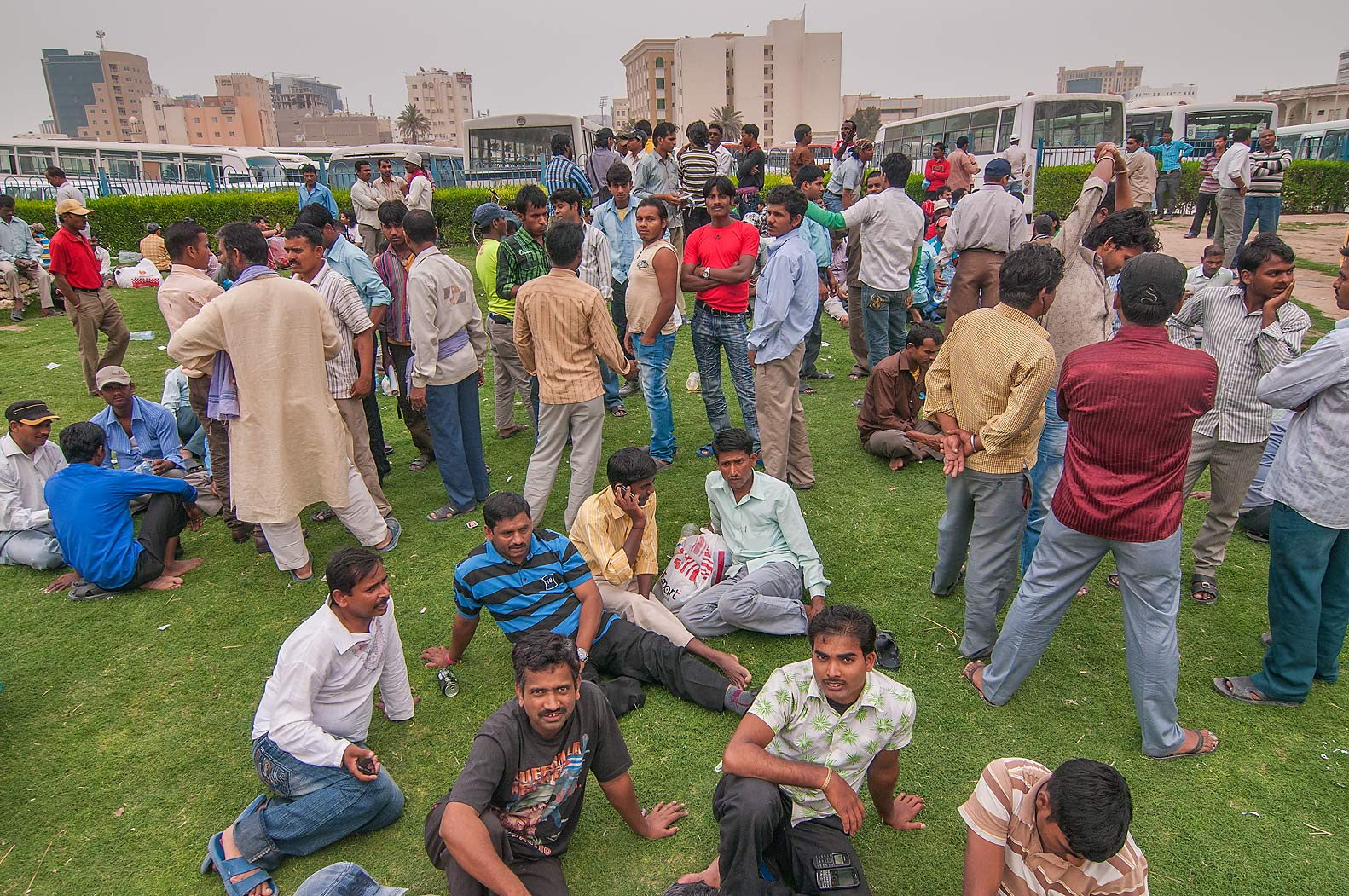Migrant workers socializing on a lawn near Central Bus Station Al Ghanim. Doha, Qatar