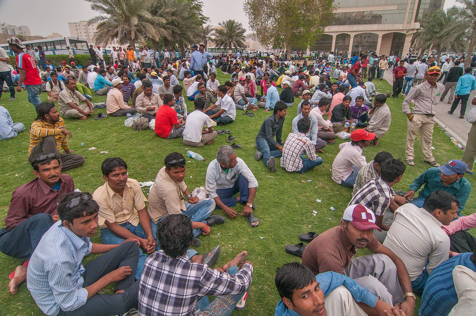 Masses of migrant workers gathering on a lawn...Bus Station Al Ghanim. Doha, Qatar