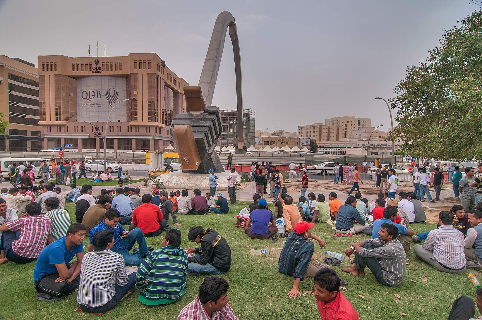 Migrant workers socializing on a lawn around...Al Ghanim on Friday. Doha, Qatar