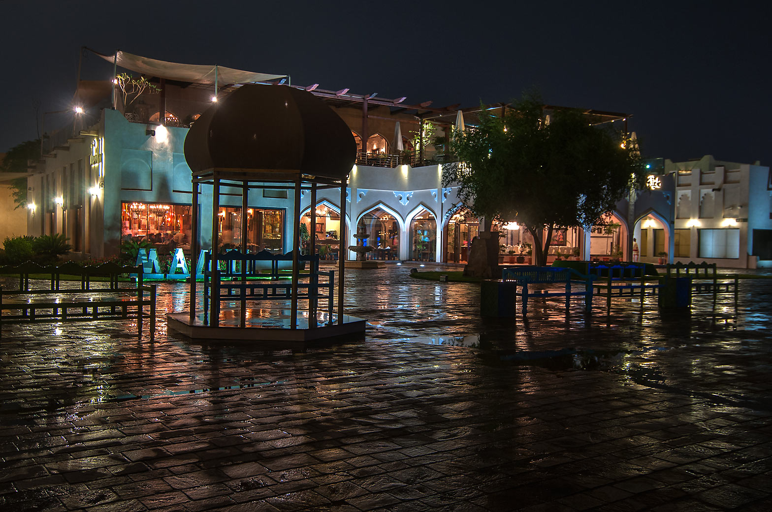 Reflections of seashore restaurants in Katara Cultural Village at rain. Doha, Qatar