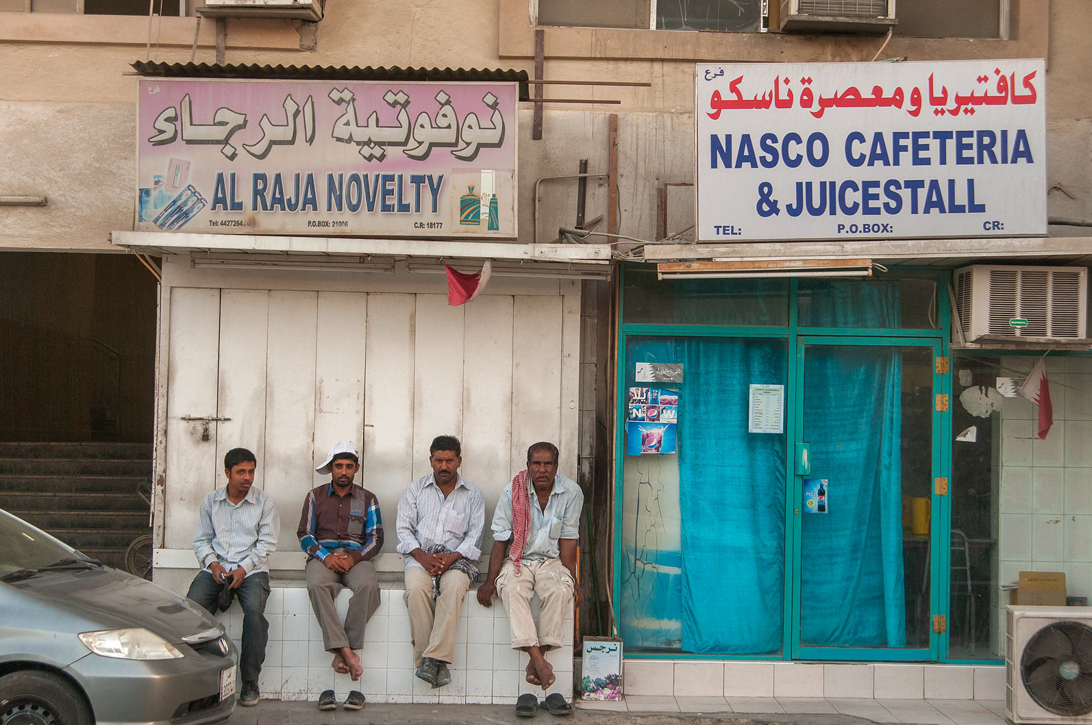 People sitting near Nasco Cafeteria and Juice...St., Musheirib area. Doha, Qatar