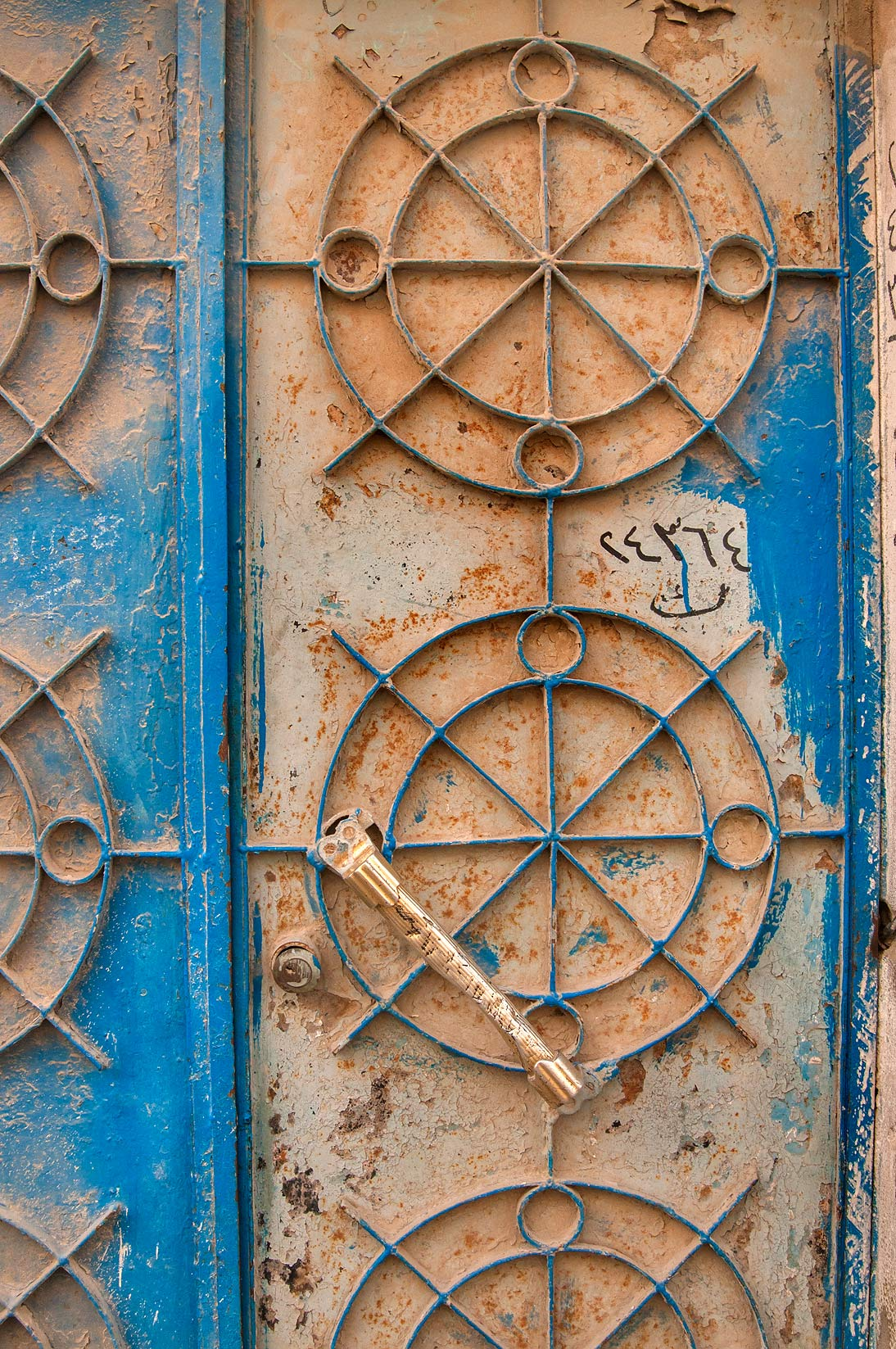 Iron door decorated by concentric circles at...Mansoura St., Najma area. Doha, Qatar
