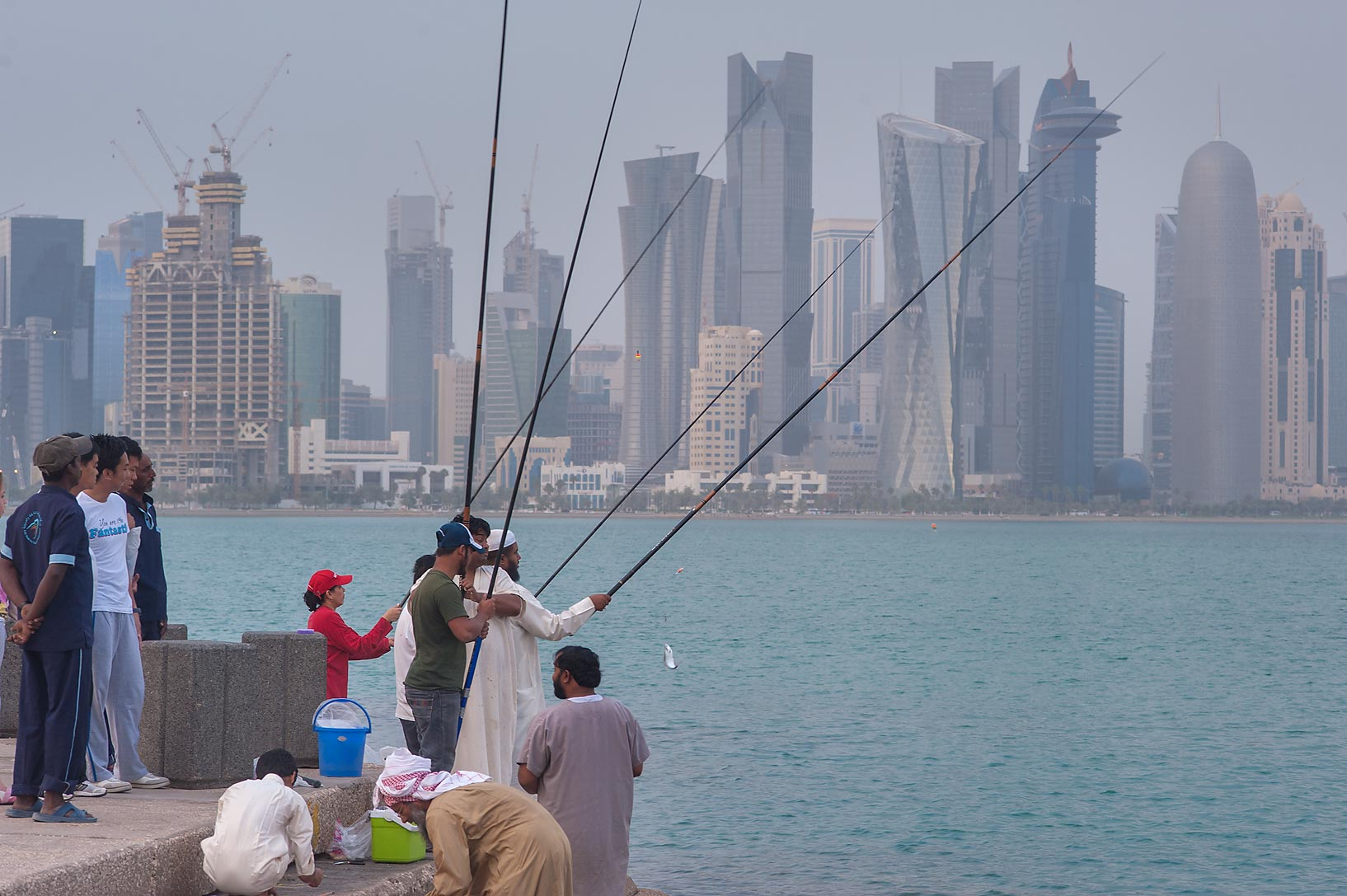 Fishing from Corniche, with West Bay in background. Doha, Qatar