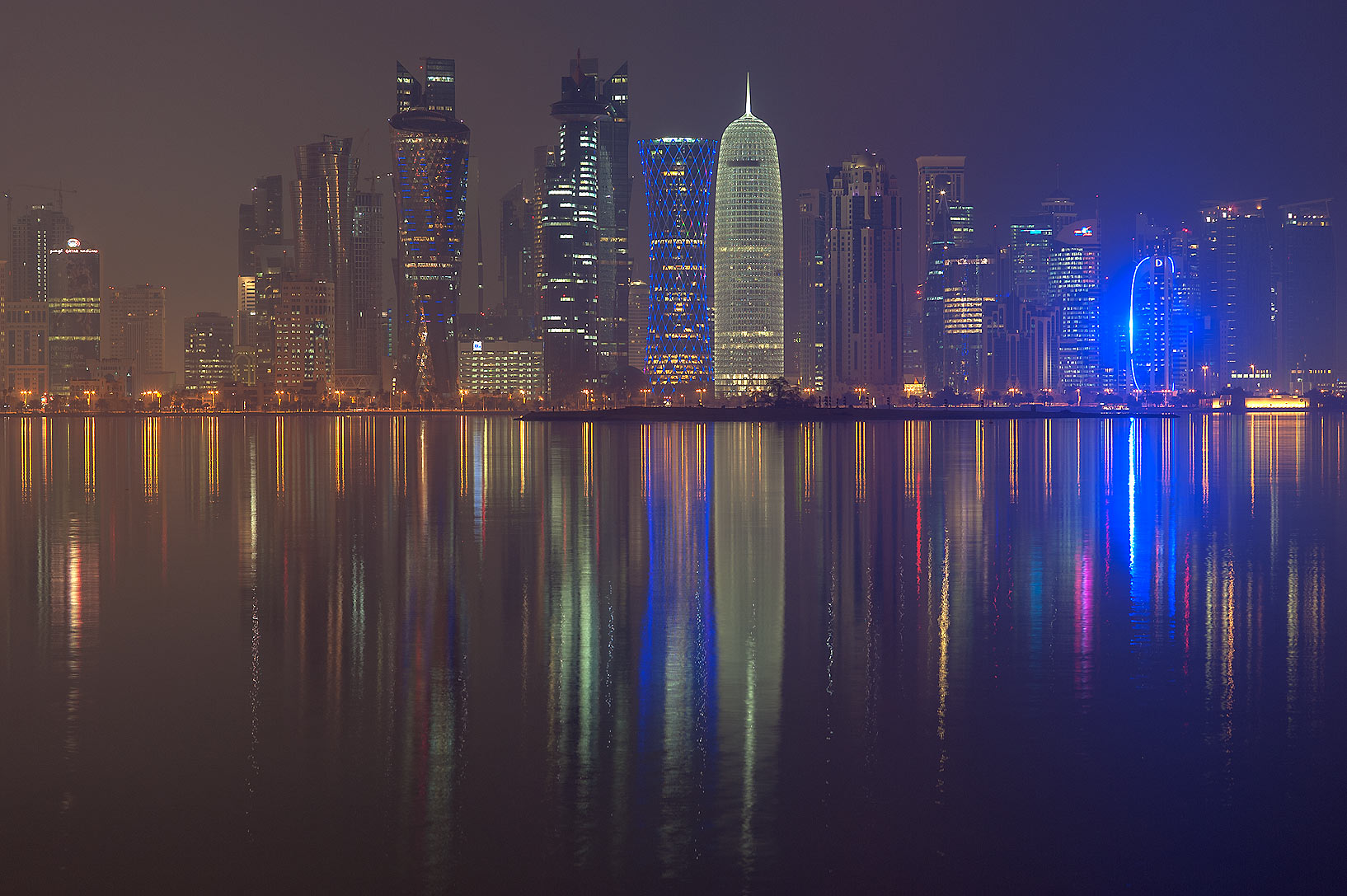 Reflections of lights of West Bay towers from Corniche promenade. Doha, Qatar