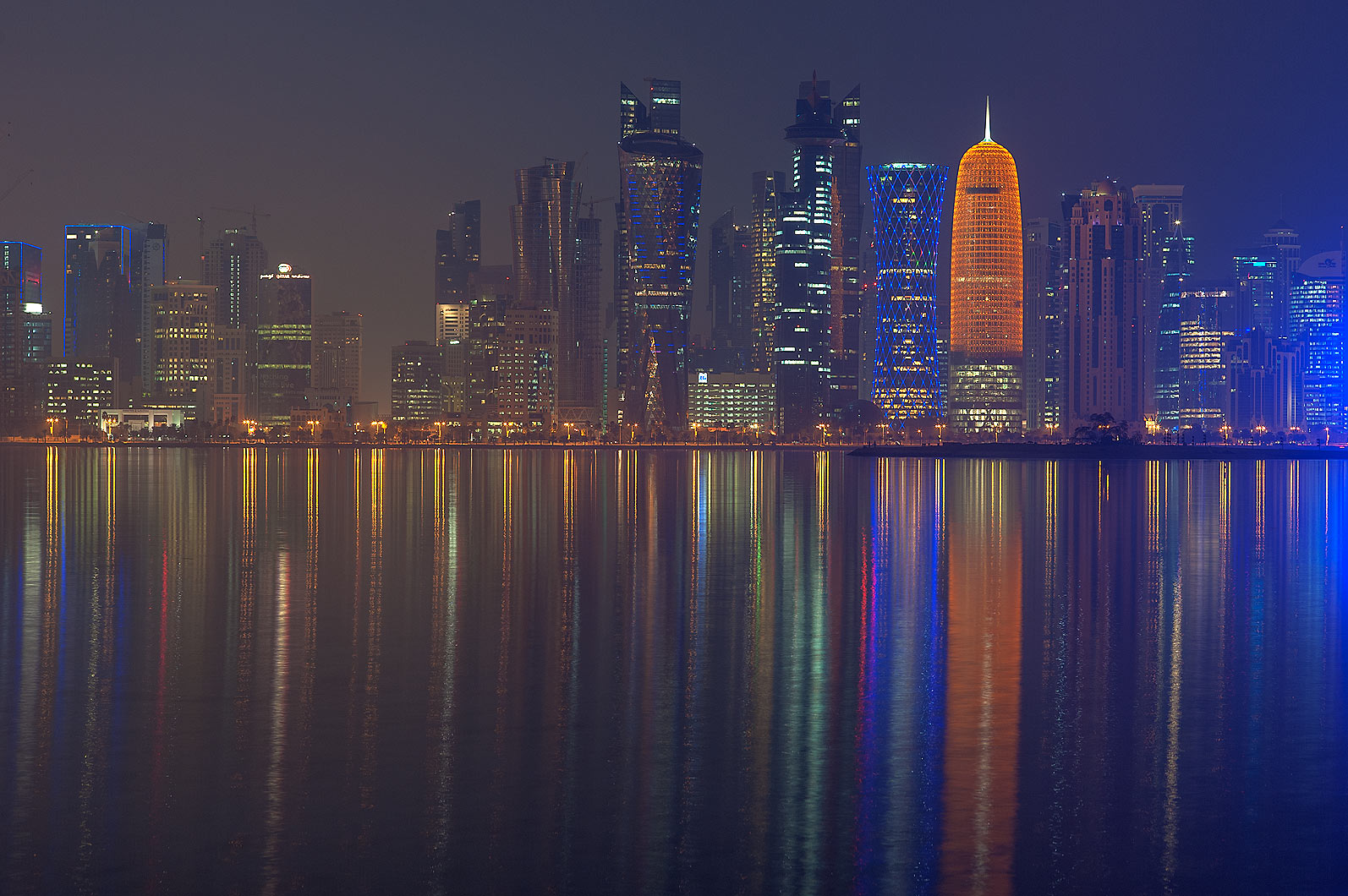 Reflections of lights of West Bay towers from Corniche promenade at dusk. Doha, Qatar
