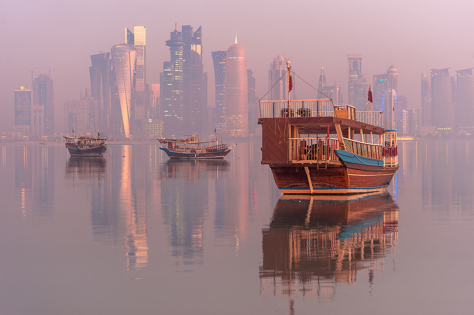 Reflections of dhow boats and West Bay towers from Corniche promenade in mist. Doha, Qatar