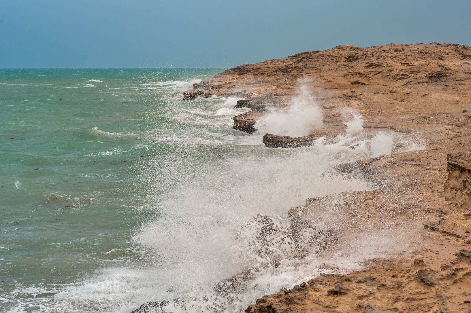 Rocky beach near Jebel Fuwairit at windy day. Northern Qatar