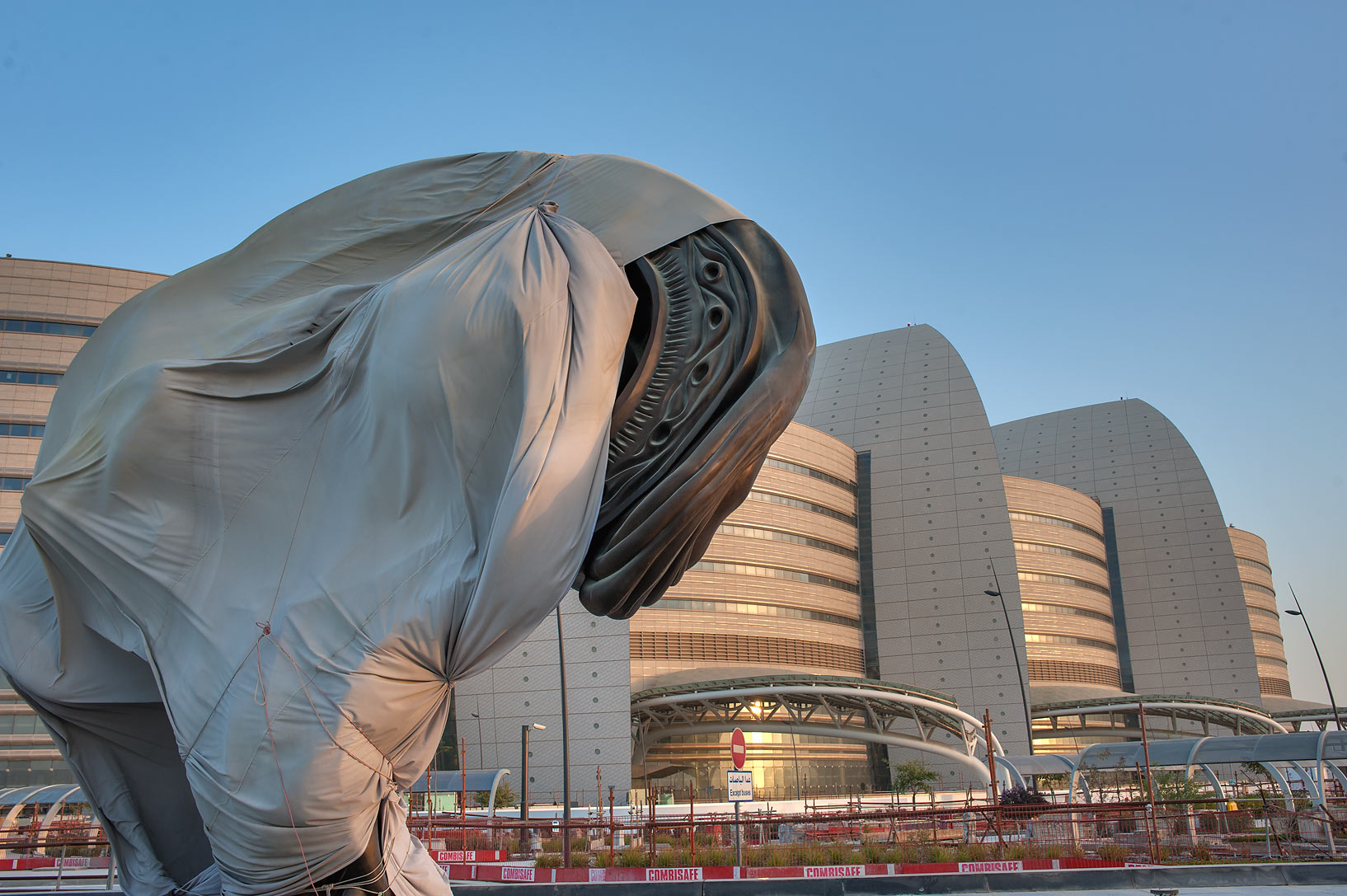 Fragment of a bronze fetus appearing from a bag...and Research Center. Doha, Qatar