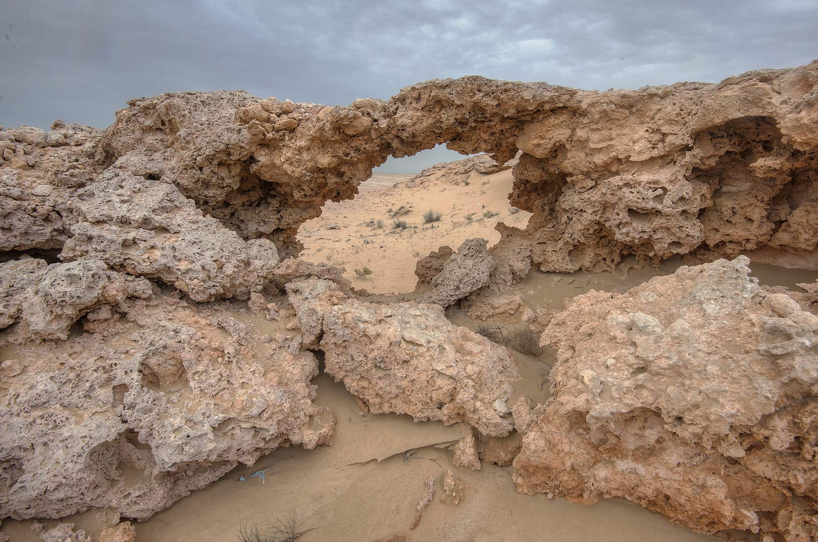 Small limestone arch on a mountain slope in Harrarah (Al Kharrarah). Southern Qatar