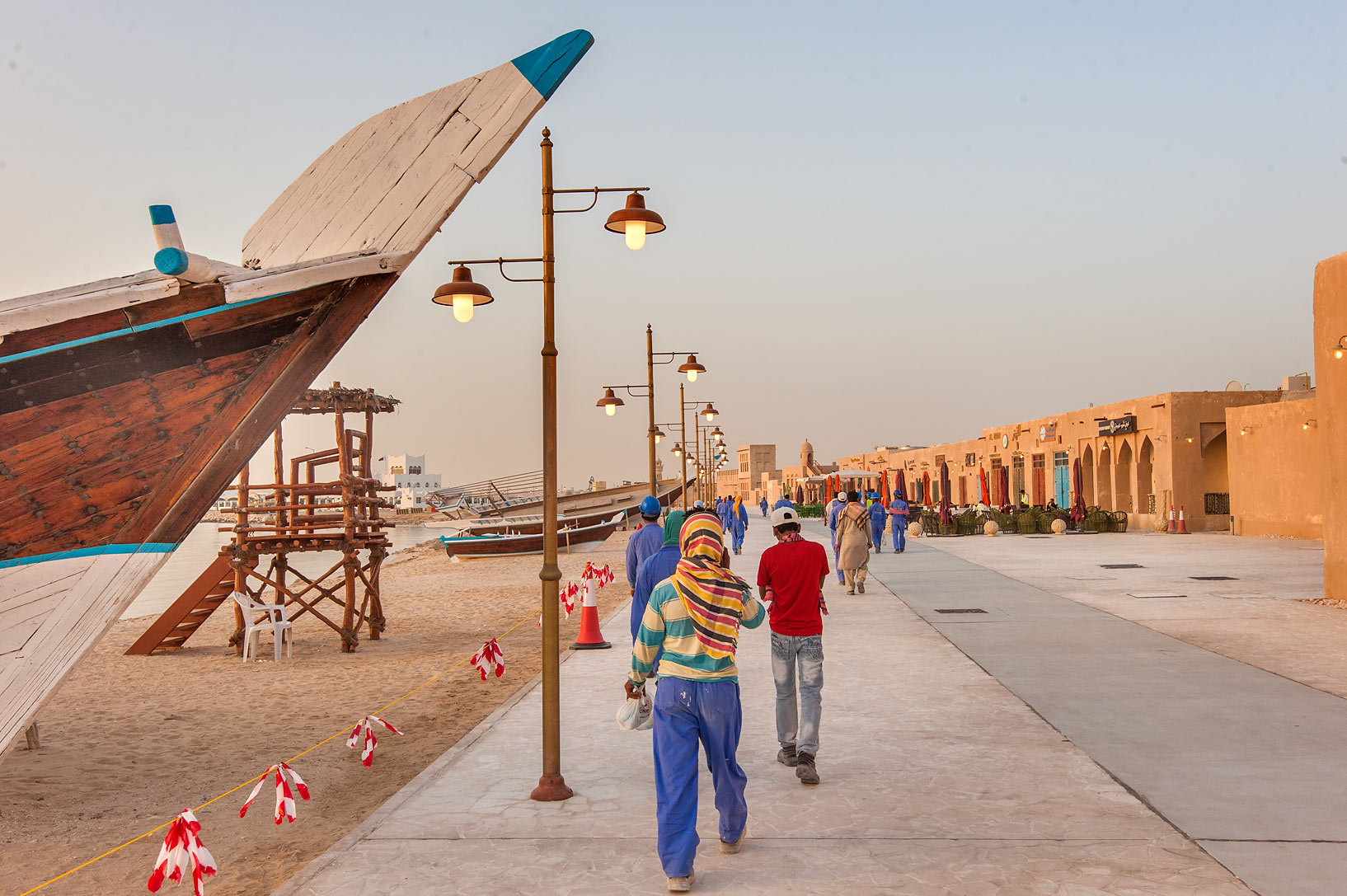 Workers walking on Corniche promenade at morning...Souq Waqif in Al Wakrah). Qatar