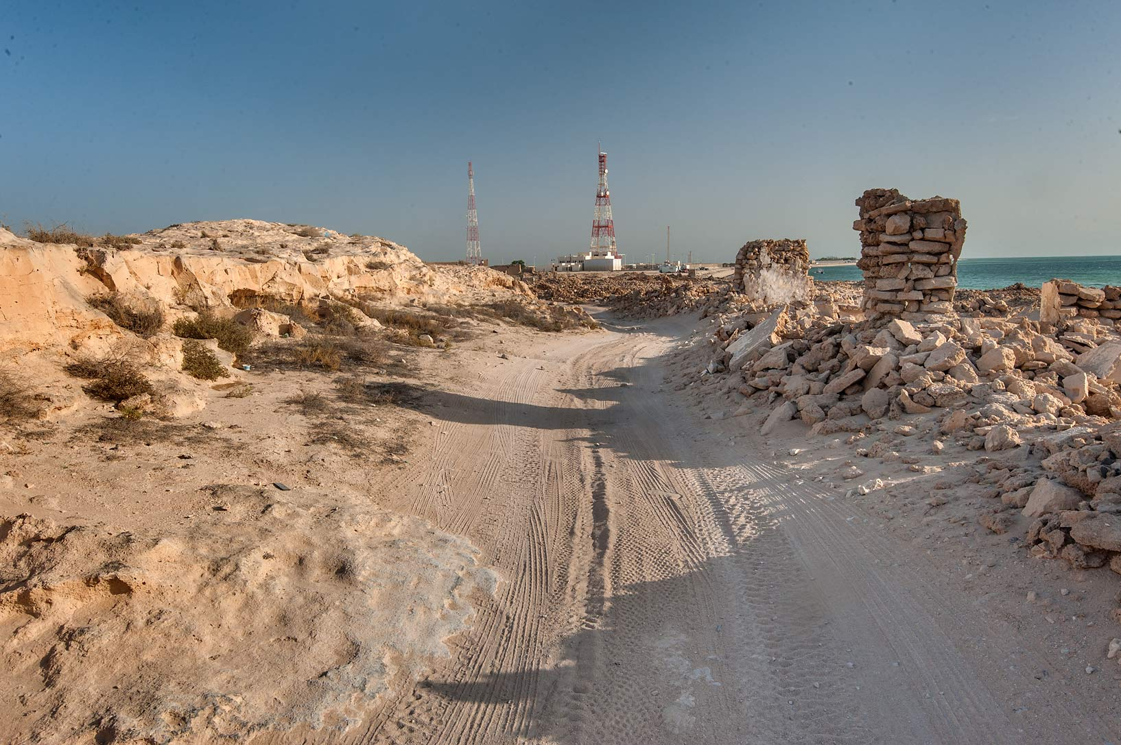 Road between a jebel (stone hill) and old fishing...eastern coast, Ash Shamal area. Qatar