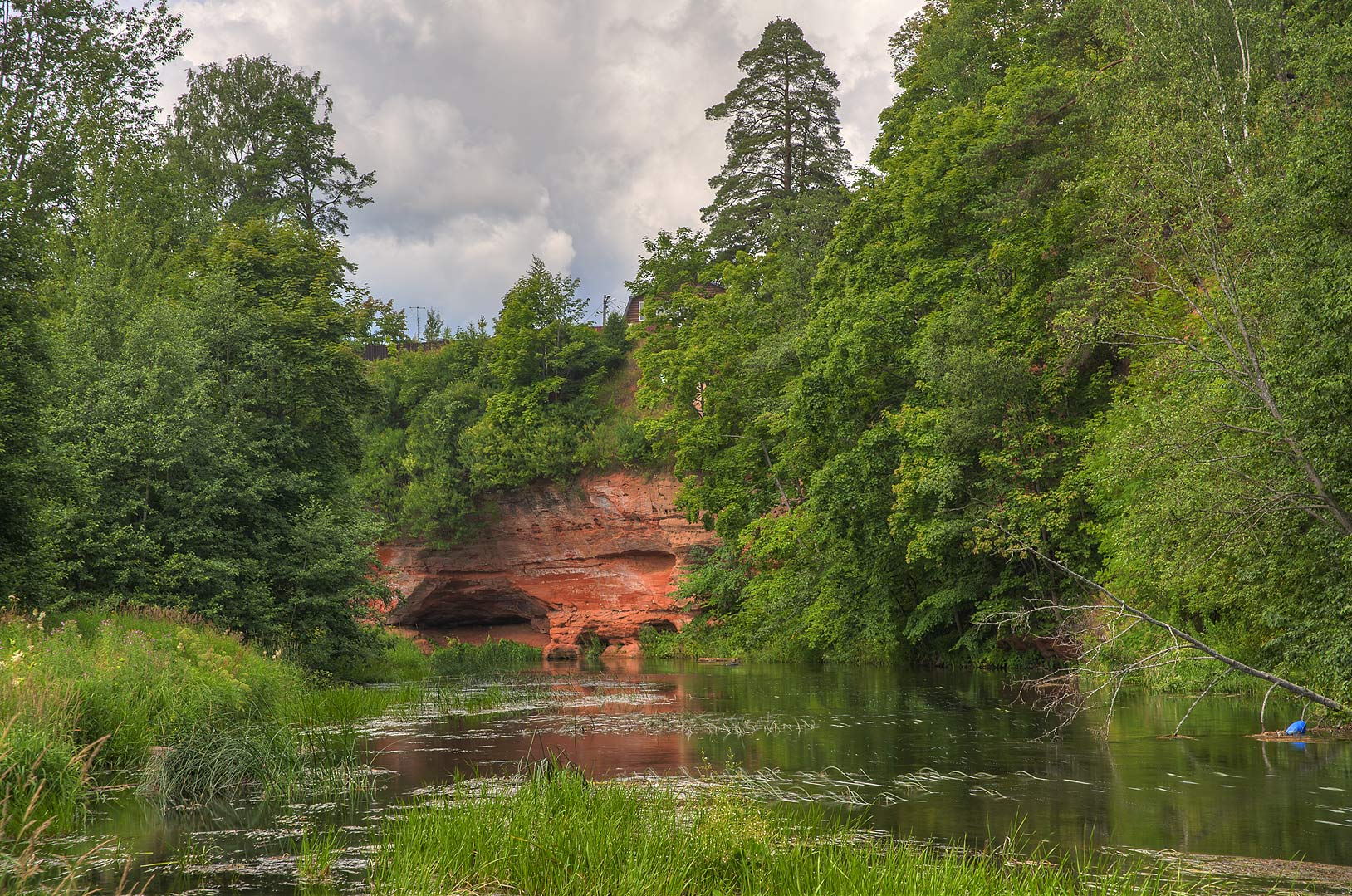Red sandstone cliff at a bend of Oredezh River...south from St.Petersburg, Russia
