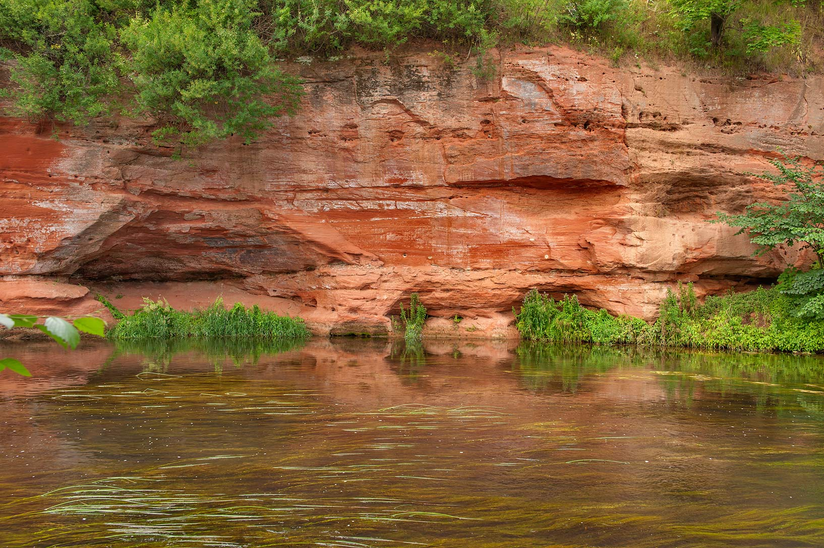 Red sandstone cliff facing Oredezh River. Siverskaya south from St.Petersburg, Russia