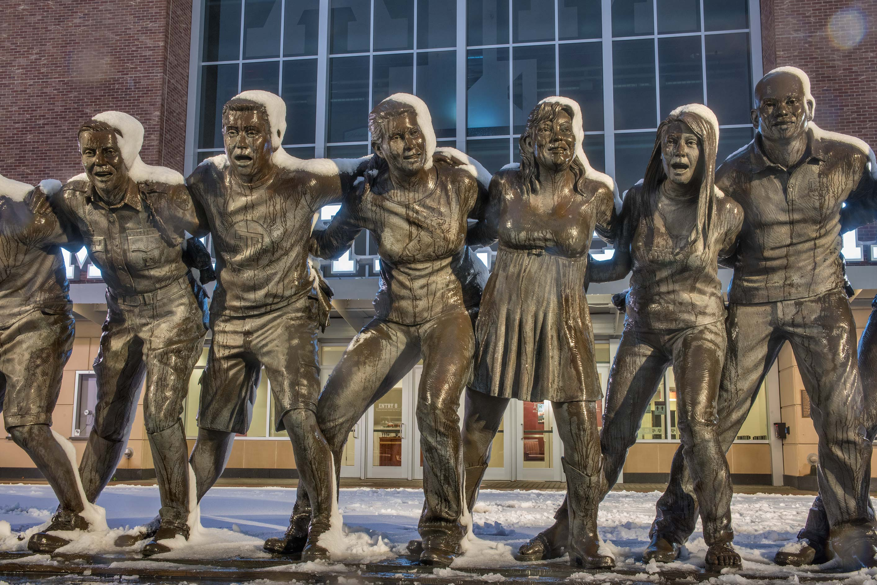 Bronze figures of 12 students covered by wet snow...M University. College Station, Texas