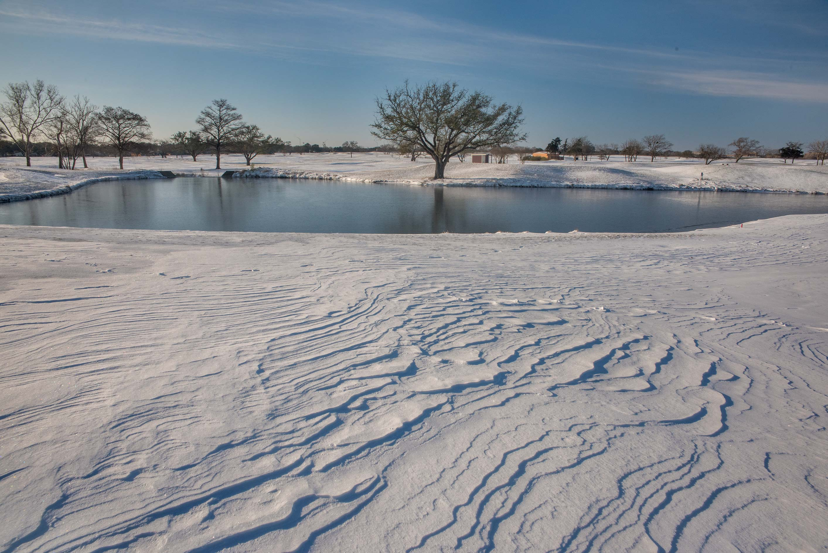 Windblown snow and ponds on a golf course on...M University. College Station, Texas